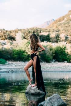 Woman in Black Two Piece Bikini Standing on the Gray Rock on the Body of Water during Daytime #33681