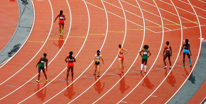 Women Standing on Race Track While Preparing for a Run Race during Daytime Free Photo