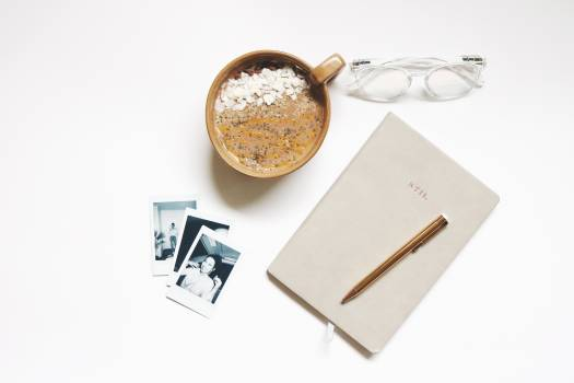 Brown Ceramic Cup Beside Notebook and Pen #336952