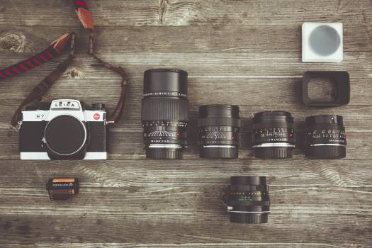 Black and Gray Dslr Camera With Assorted Lenses on Brown Wooden Surface Free Photo