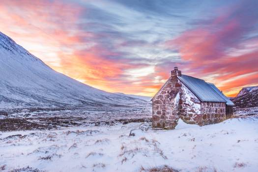 Brown House Surrounded by Snow Covered Field Near Snow Covered Mountain Under Yellow Blue and Orange Sunset #33744