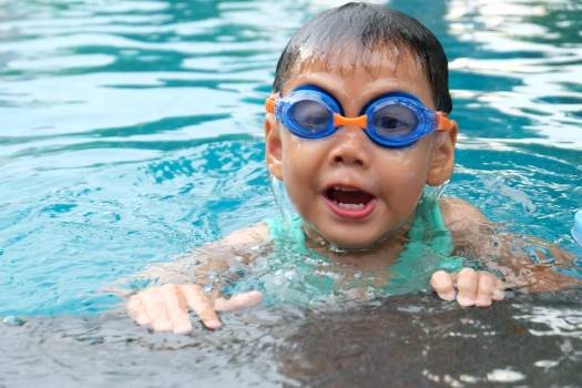 Toddler Swimming on Pool Wearing Blue Goggles #337509