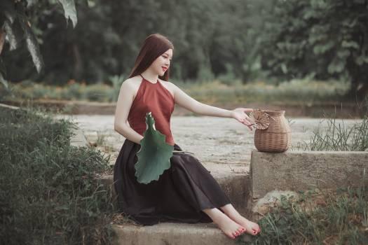 Woman Sitting on Star Beside Brown Wicker Basket Durng Daytime #337843