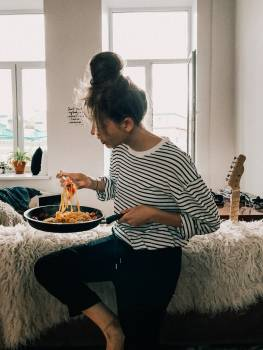 Woman in Black and White Striped Shirt Eating Food from Pot Free Photo