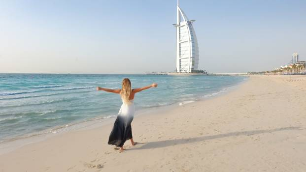 Photography of Woman Walking On Seashore Free Photo