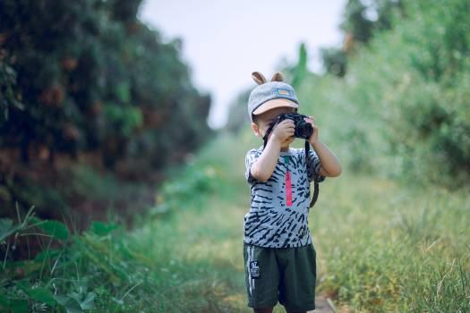 Boy Using Camera Near Green Leaf Plants Free Photo