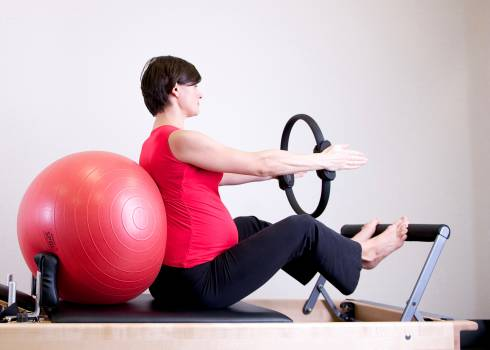 Woman in Red Shirt Sitting on Fitness Equipment Free Photo