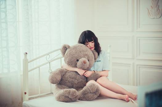 Woman Hugging Gray Bear Plush Toy on White Mattress #338331