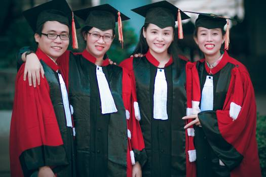 Man and Women Wearing Red-and-black Academic Gowns and Black Mortar Boards Free Photo