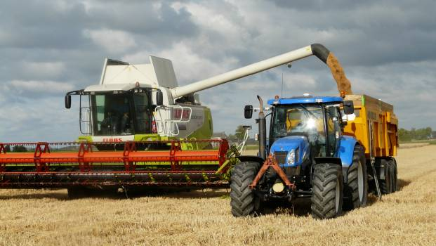 Blue Tractor Next to White Farm Vehicle at Daytime Free Photo