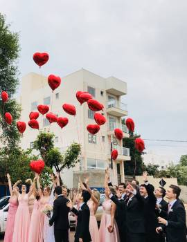 Women Wearing Pink Dresses and Men Wearing Black Suit Jacket and Pants Raising Hands With Red Heart Balloons Free Photo
