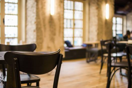 Black Wooden Tables and Chairs Arranged Inside Restaurant With Yellow Sconce Free Photo