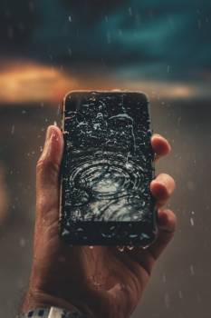 Photo of Person Holding Wet Smartphone Free Photo
