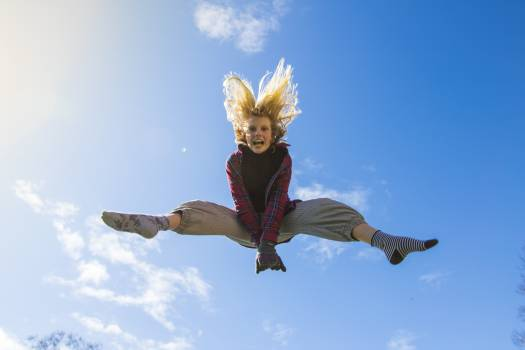 Woman Jumping Under Blue Sky Free Photo