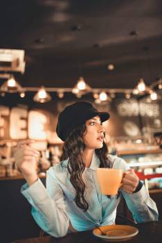 Woman Holds Hot Beverage Cup at the Restaurant Free Photo