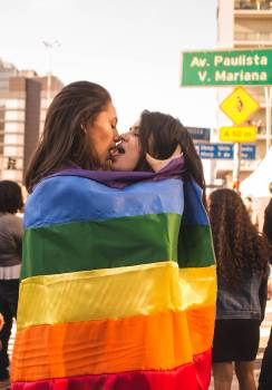 Two Women Kissing While Wrapped in Rainbow Flag Free Photo