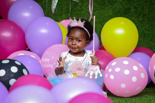 Toddler Girl Sitting On Ground Surrounded By Balloons Free Photo