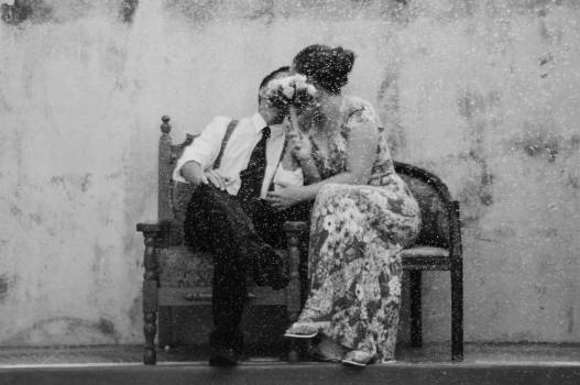 Gray scale photography of a couple kissing covering their faces with Bouquet of Flower Free Photo