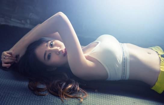 Woman Wearing White Sport Bra Lying on Black Mat #340546