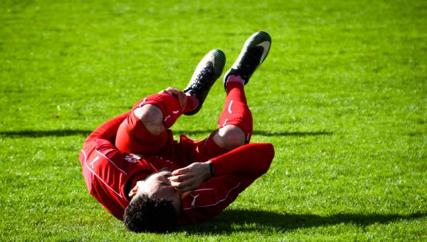 Soccer Player Lying on Ground While Holding His Leg #340560