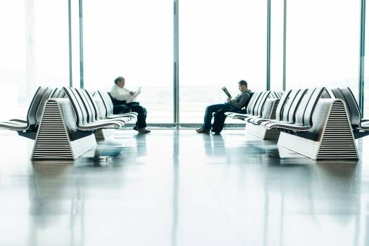 Two Men Sitting in Front of Each Other on White Gang Chairs in Airport Waiting Area Free Photo