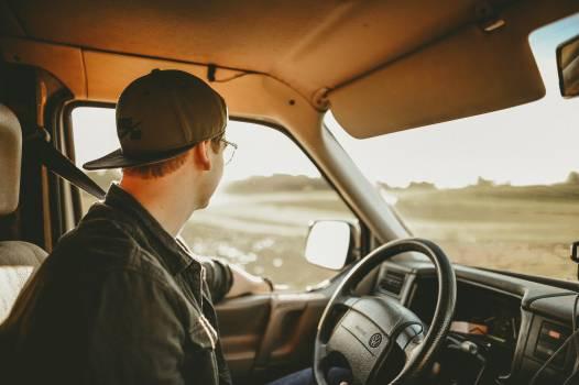 Man Wearing Black Denim Jacket in Driver's Seat Free Photo