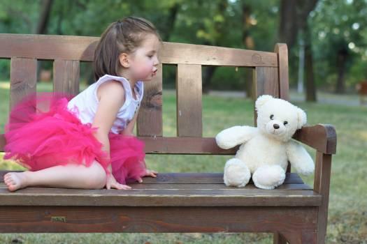 Brown Haired Girl Wearing Pink Tutu Dress Near White Bear Plush Toy Free Photo