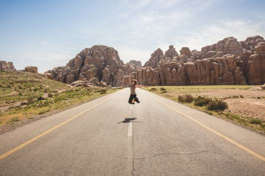 Woman in Brown Shirt Jumping Shot in Middle of Gray Asphalt Road Photography during Daytime #34147