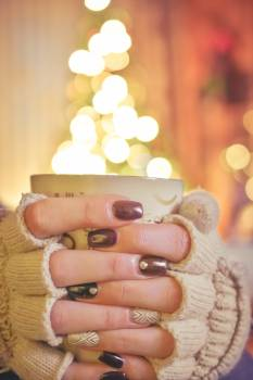 Person Holding a Mug Infront of a Lighted Christmas Tree Free Photo