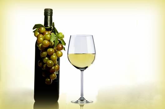 Wine in Wine Glass Near Green Glass Bottle #341753
