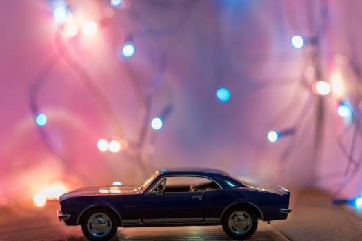 Selective Focus Photography of Classic Blue Coupe Die-cast Model in Front of String Lights on Table Free Photo