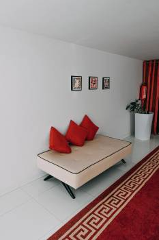 Three Red Throw Pillows on White Sofa in Room #342271