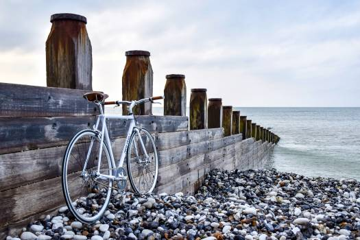 White Road Bike Beside the Brown Wooden Gate Besode the Sea #34241