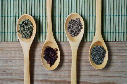 Brown Wooden Spoon With Herbs on Top of Green Bamboo Mat and Brown Wooden Surface #34432
