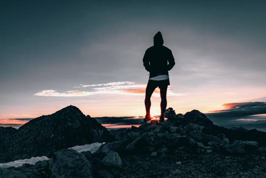 Person in Black Hoodie Standing on Rocks during Dusk Free Photo