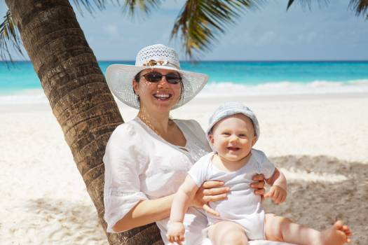 Woman Holding Infant on Beach Free Photo
