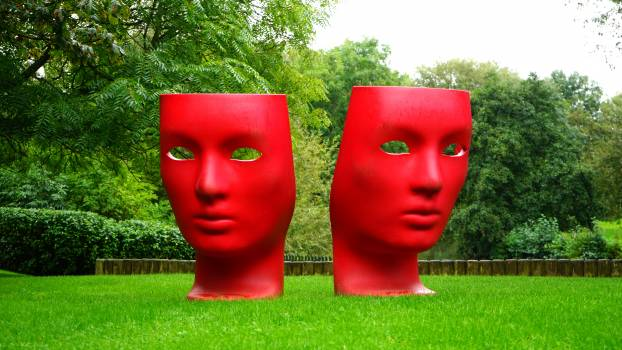 Red Human Face Monument on Green Grass Field #34602
