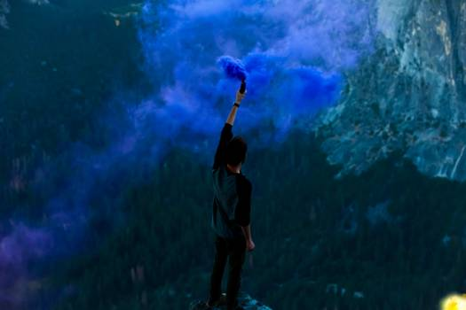 Man Holding Bottle With Blue Smoke Standing on Cliff during Daytie #34767
