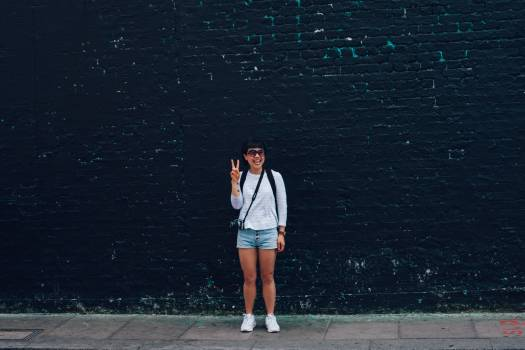 Woman in Blue Denim Shorts Standing in Front of Black Brick Wall #34909