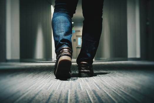 Person in Blue Denim Fitted Jeans Walking Through Hallway Free Photo