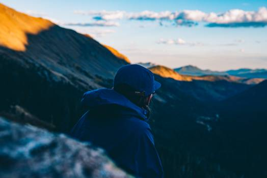 Man in Blue Hoodie Standing on Mountain Cliff during Daytime #35345