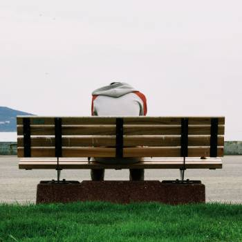 Person Wearing Grey and Orange Hoodie Sitting on Brown Wooden Park Bench during Daytime #35943