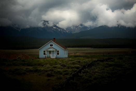 Gray and Brown Roof House in the Middle of Green Grass Field Near Mountains Photo #36250