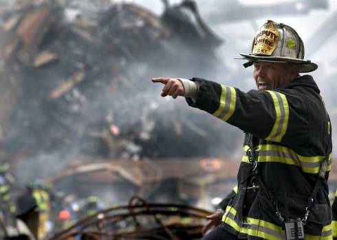 Fire Fighter Wearing Black and Yellow Uniform Pointing for Something #36383
