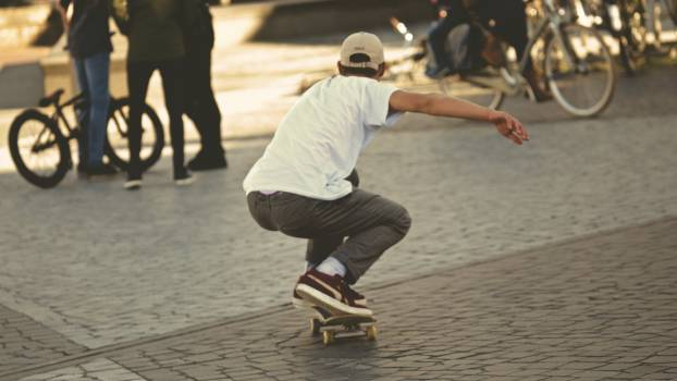 Man in White Shirt and Brown Jeans Riding Skateboard #36752