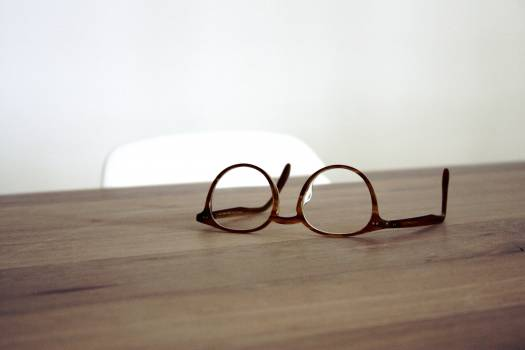 Brown Framed Glasses on a Wood Table Free Photo