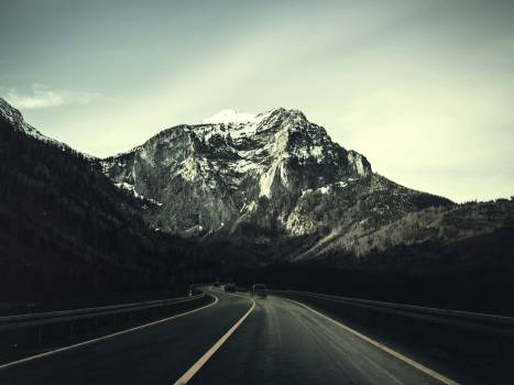 Asphalt Road With Running Vehicle Infront of Mountain Under Gray Sky Free Photo