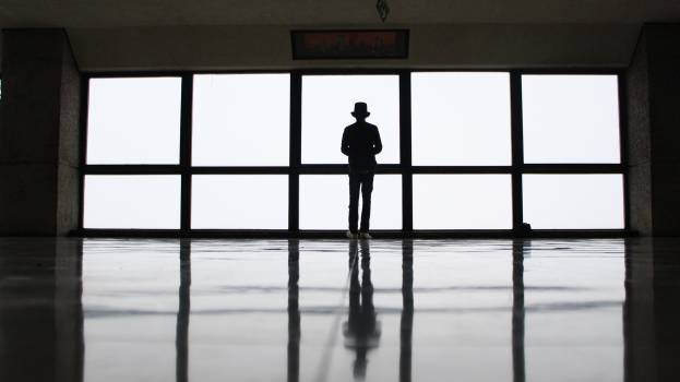 Silhouette of Man Wearing Hat Standing Near Window during Daytime Free Photo