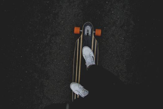 Person Showing White Sneakers and Riding Black Orange and White Skateboard #37507