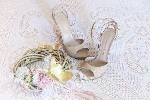 Women's White Stiletto Sandals on White Floral Design Textile Free Photo